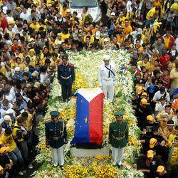 """The coffin of the late former Philippines president Corazon Aquino proceeds through a crowd of Filipinos during the democracy icon's funeral procession in Manila Wednesday. At least 150,000 people took to the rain-soaked streets of Manila on Wednesday to bid farewell to former president Corazon Aquino, whose """"People Power"""" democracy movement ended decades of dictatorship."""