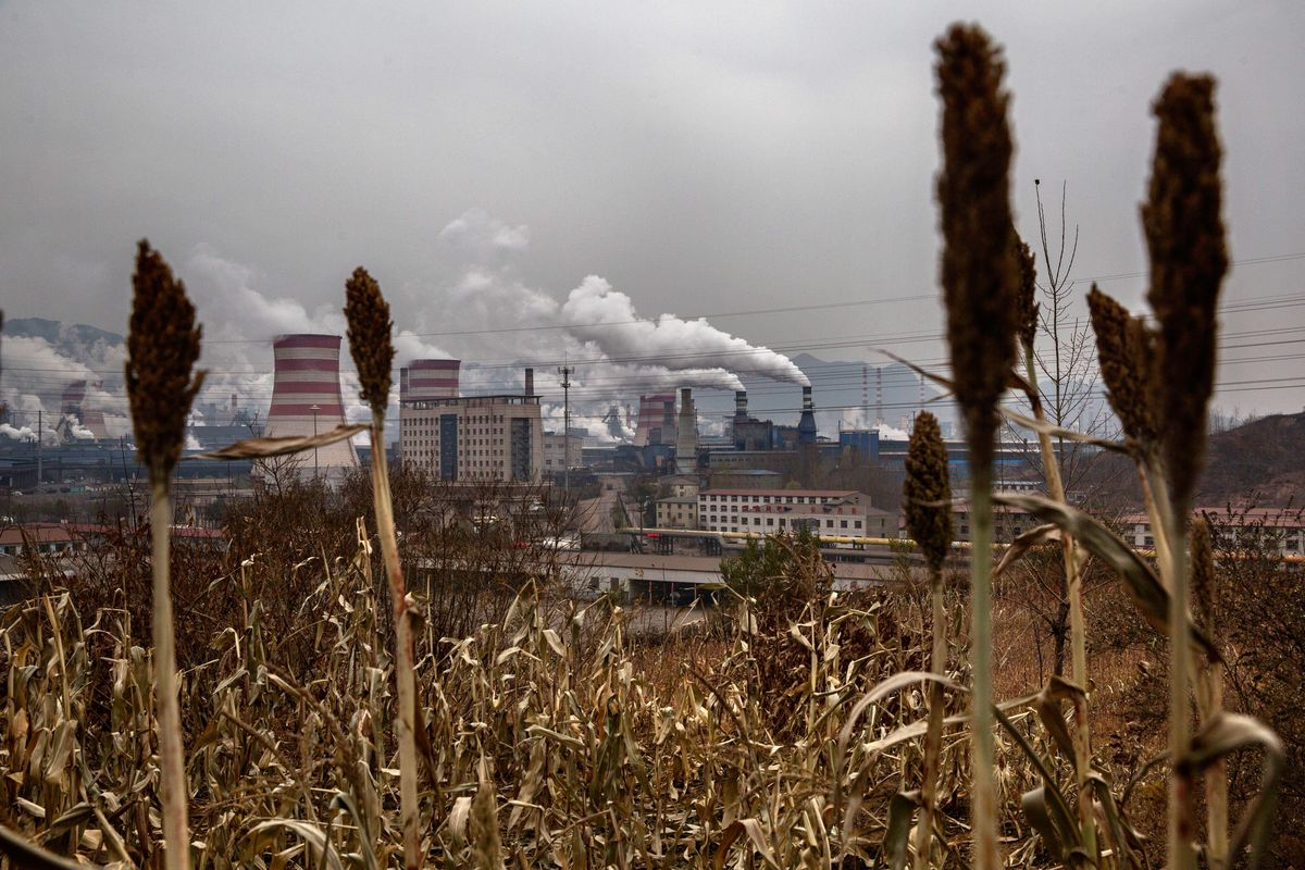A steel mill in China behind fields of wheat