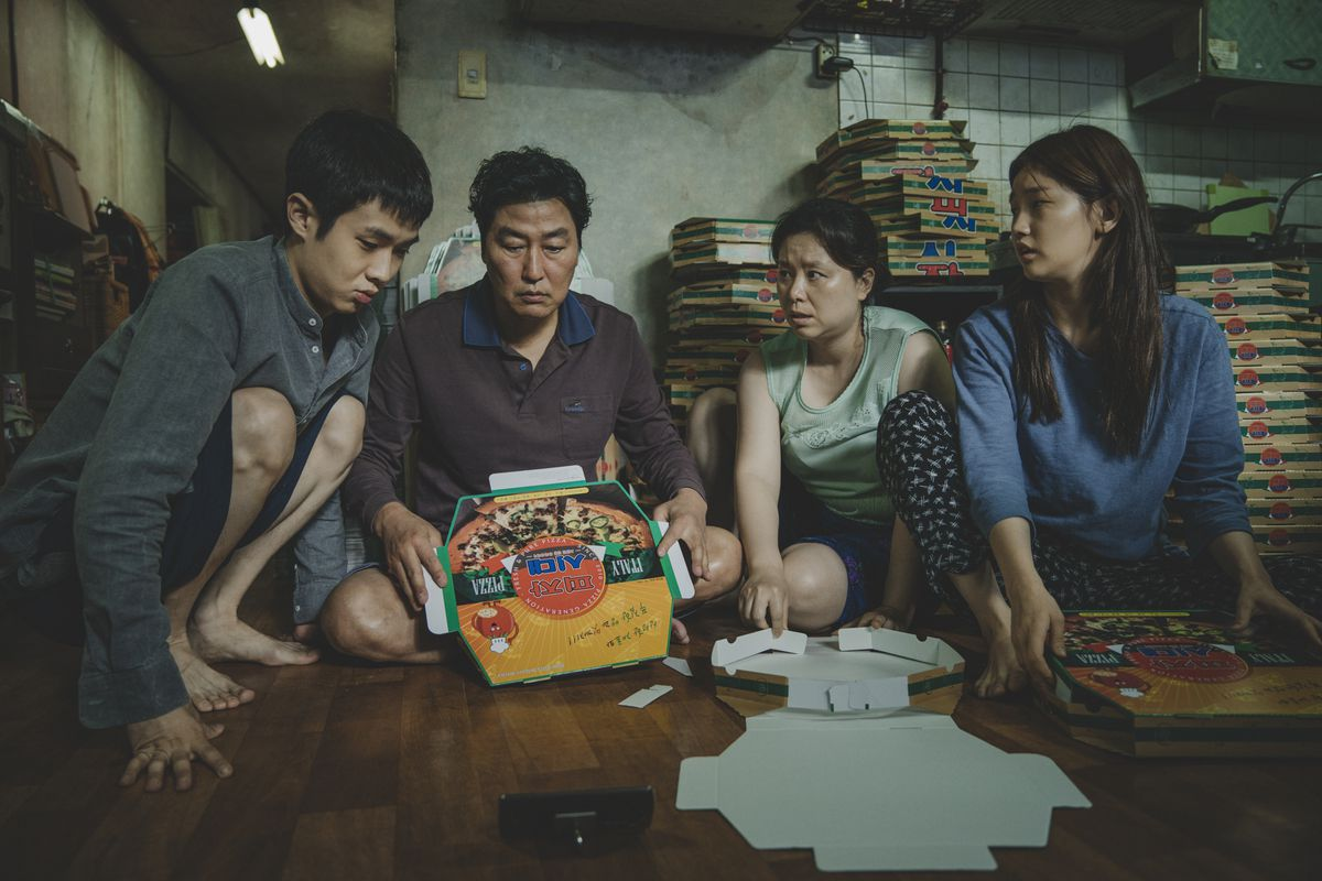 Korean son, dad, mother and daughter are sitting in their small apartment folding pizza boxes in Parasite