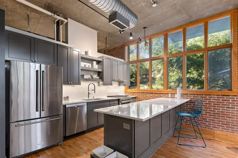 A white and gray kitchen with a huge brick wall at right.