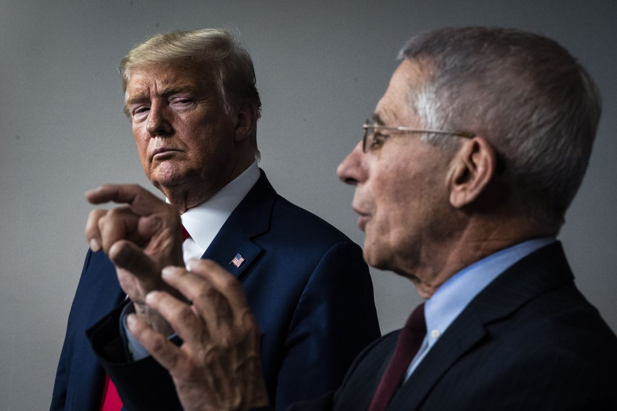 Trump, standing behind Fauci, appears stern. Fauci, in the foreground, raises his hands as he answers a question.