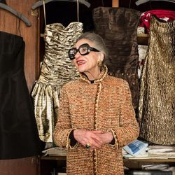 """Joy Venturini Bianchi wearing a Chanel coat, (""""I call it """"channel"""") and surrounded by dresses left to right: Michael Kors, Ralph Lauren Collection, Victor Costa for Bergdorf Goodman, Ralph Lauren, Ralph Lauren Collection, Moschino."""