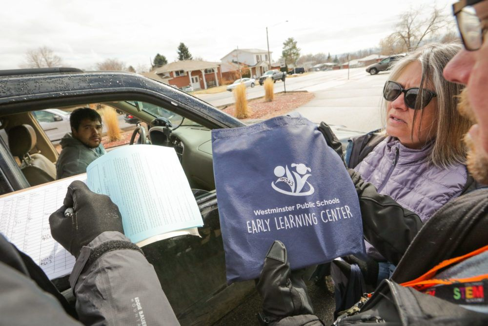 Volunteers from Sherrelwood Elementary School in Westminster hand out laptops and educational materials to parents and students on Friday, March 13, as schools prepare to close for two weeks.