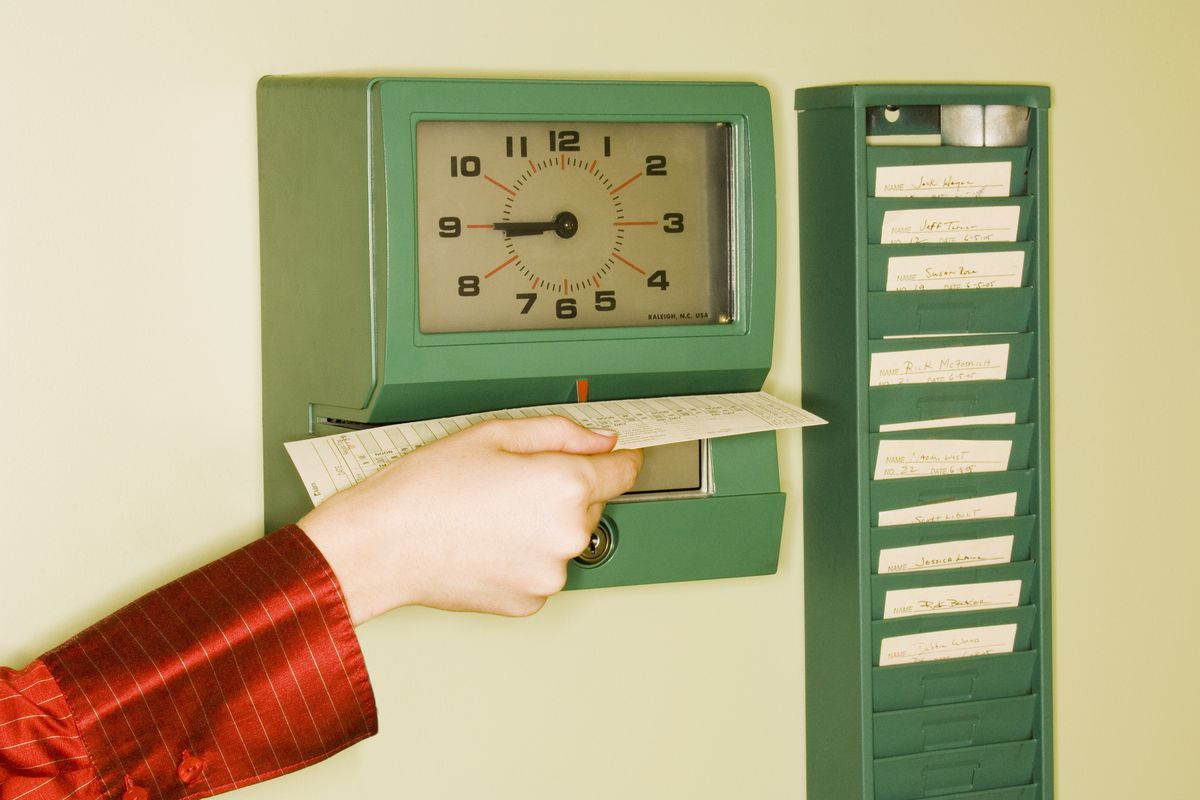 A female hand punches out on a time clock.