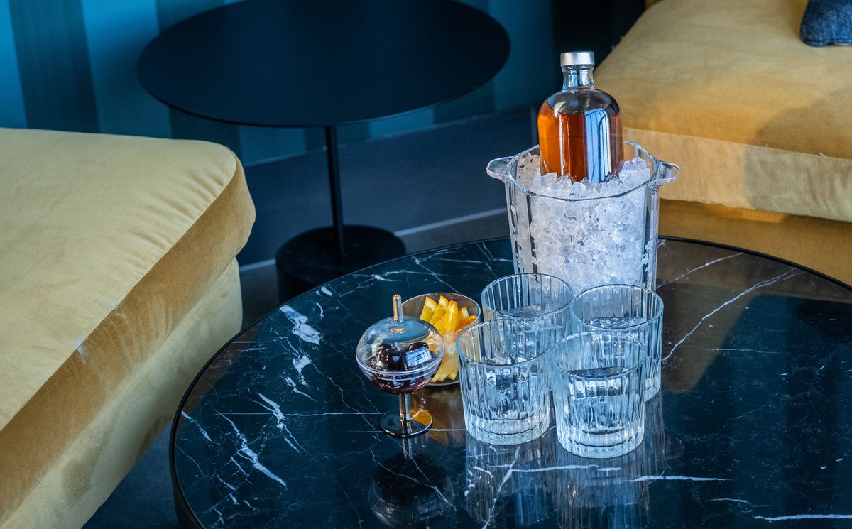A cocktail for four is presented in a bottle on ice, with four glasses ready, on a dark marble table. Yellow velvet couches are visible in the background.