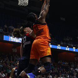 Connecticut Sun's Chiney Ogwumike (13) has her shot blocked Washington Mystics' Emma Meesseman (33).