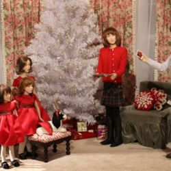 Three girls and a dog in matching dresses at Lord & Taylor