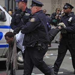 Police arrest a protester of a combined group of ACT UP and Occupy Wall Street activists who chained themaselves and block traffic at Wall Street and Broadway, near the New York Stock Exchange, on Wednesday, April 25, 2012.  Police used chain cutters and wrestled protesters to the pavement in the middle of Broadway.
