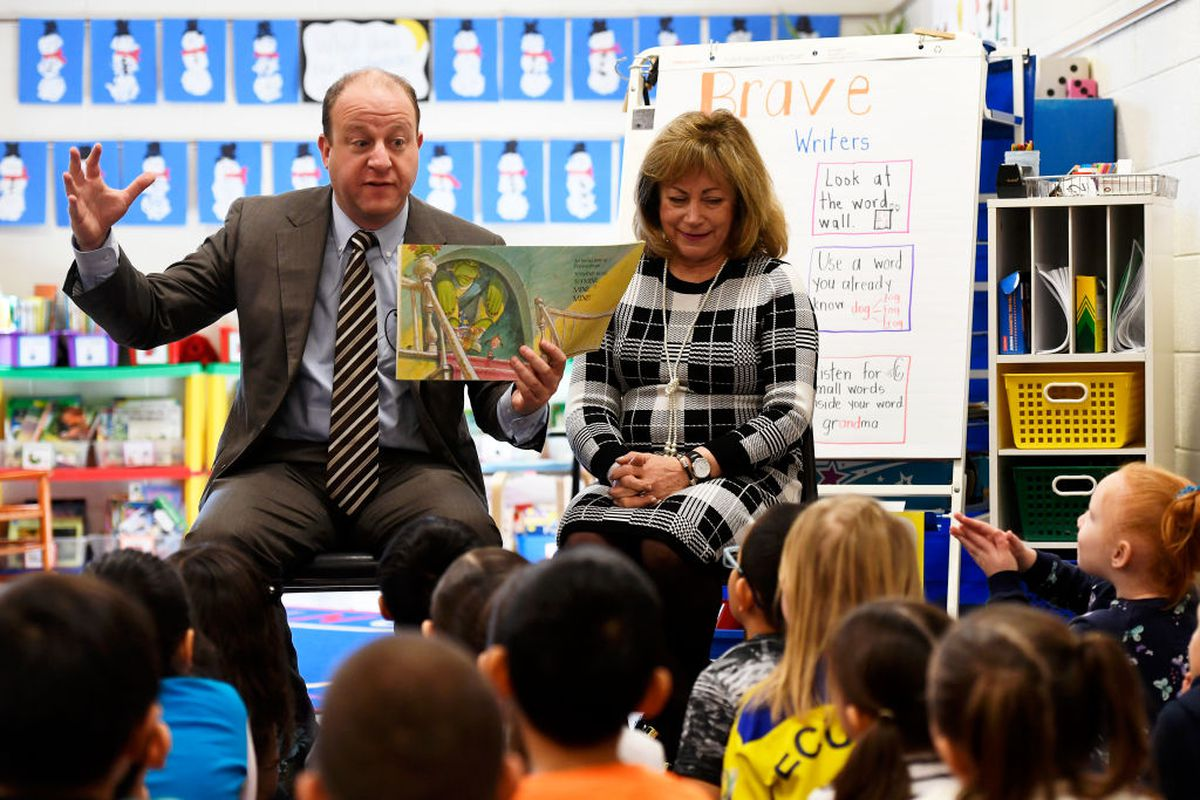 """Colorado Governor Jared Polis with Lt. Gov. Dianne Primavera beside him reads """"The Boy Who Wouldn't Share"""" to Jessica Lovato's kindergarten class at Denver's Centennial Elementary."""
