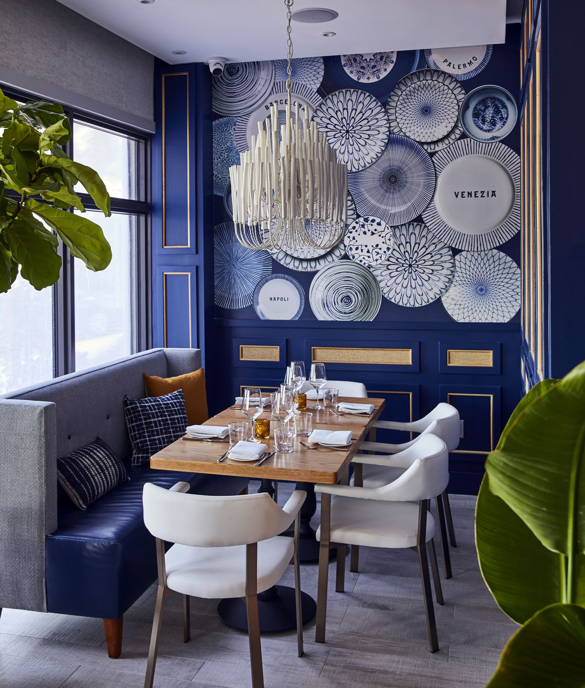 bright blue dining room with white chairs and white chandelier