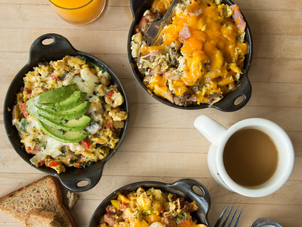 breakfast skillets topped with avocado and cheese, a white coffee mug