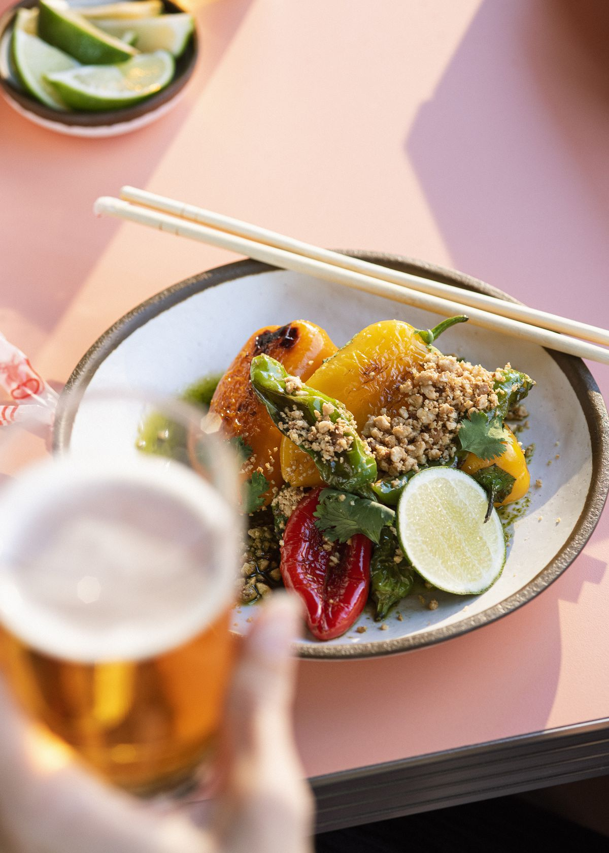Fried Peppers with cilantro, cashew, citrus salt, and a beer on a pink table