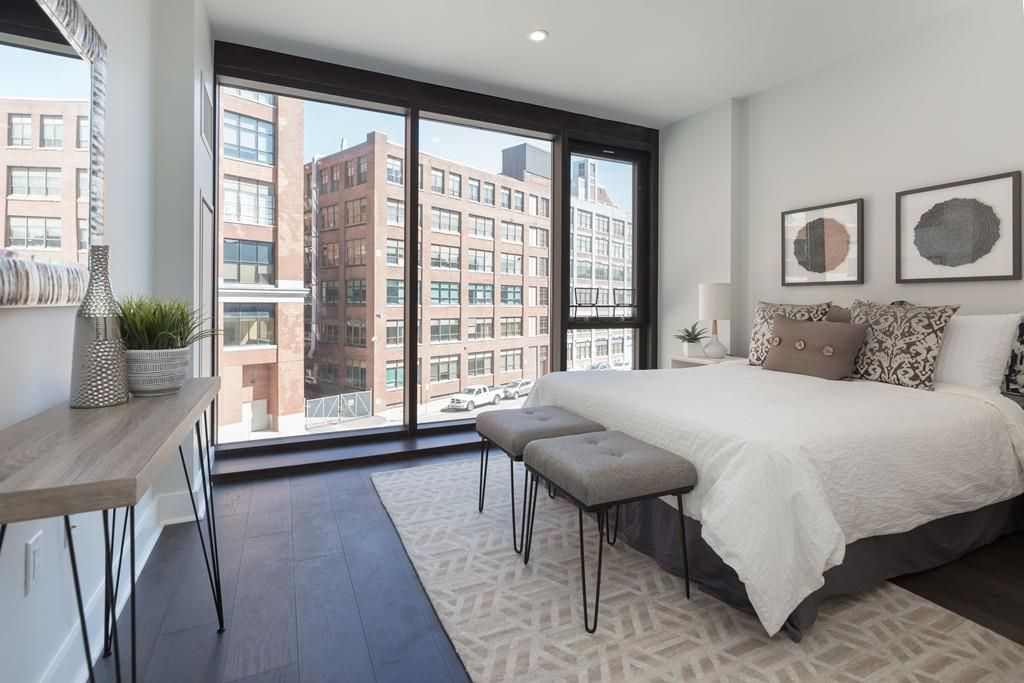 A bedroom with a bed and a table, and buildings are visible beyond the floor-to-ceiling windows.