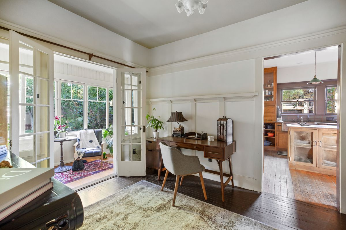 Room with French doors leading to a sun room and another door to the kitchen.