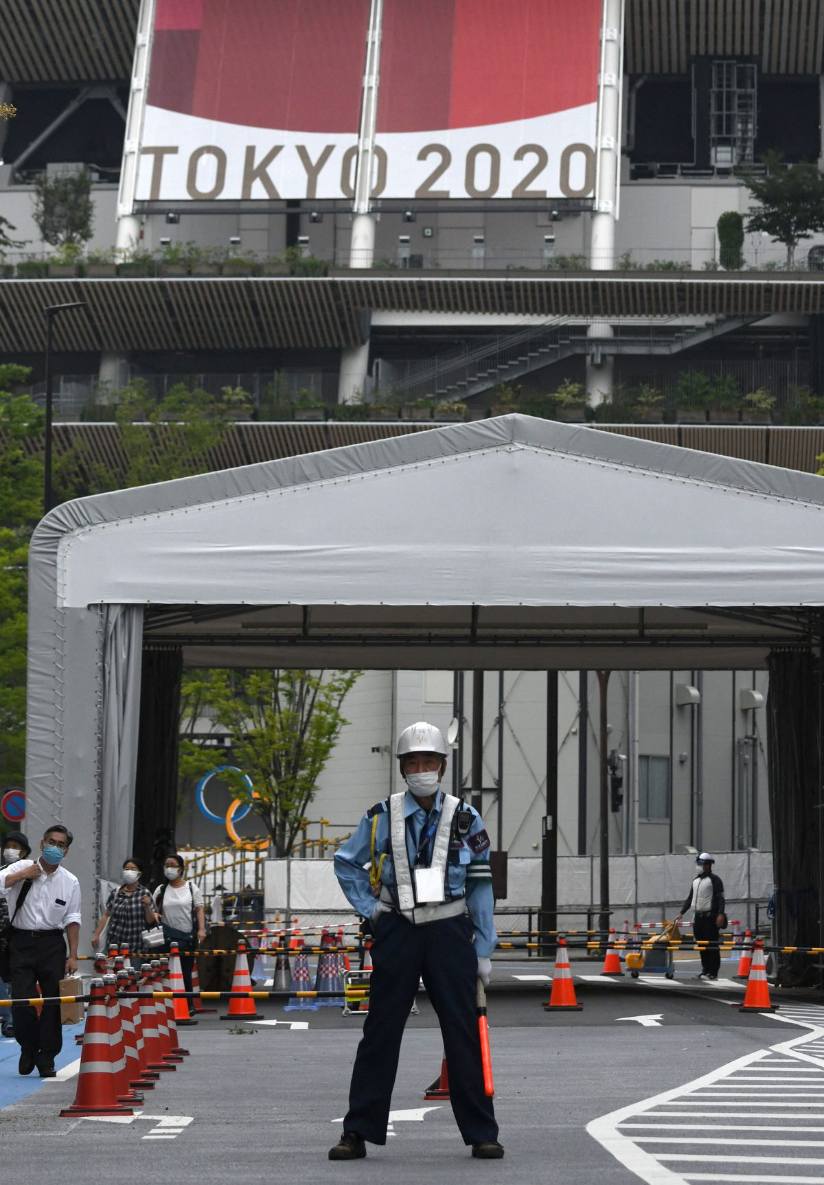 A security guard stands watch over an empty Japan National Stadium