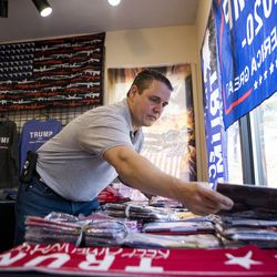Rhode Island entrepreneur Keith Lambert arranges Donald Trump flags during the opening day of his store in Bellingham, Mass., Saturday, Nov. 9, 2019.