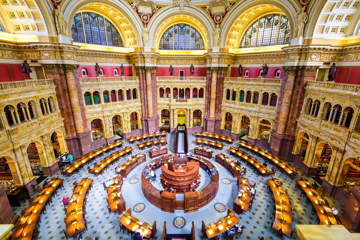 The interior of the Library of Congress. The room is circular in shape. There are arched windows and doorways. In the center of the room is a circular desk surrounded by rows of tables and chairs.