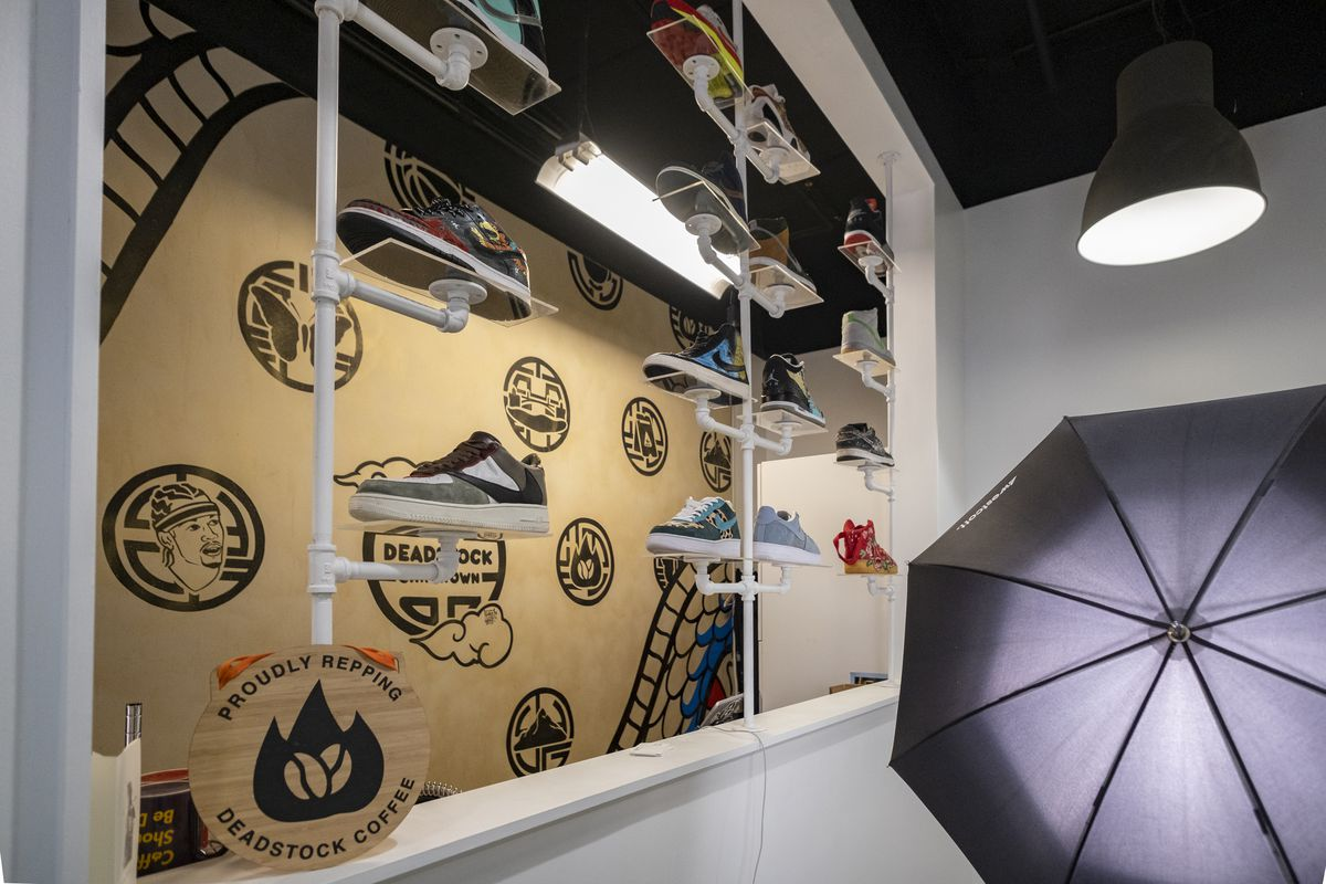 The wall at Deadstock, which is designed with black patterns. Shoes sit on mounted pipes.