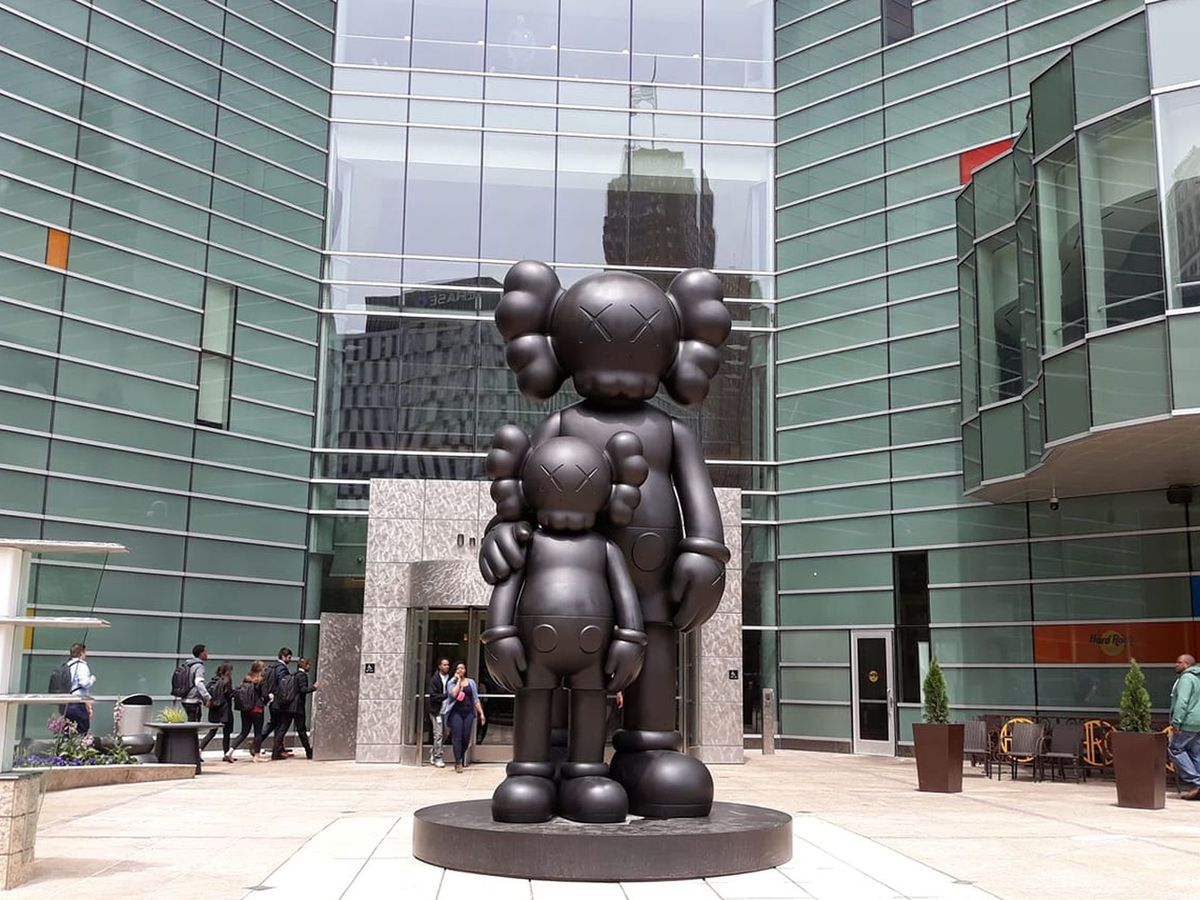 A courtyard between buildings. There is a large statue of a parent and child. The figures are cartoonish.