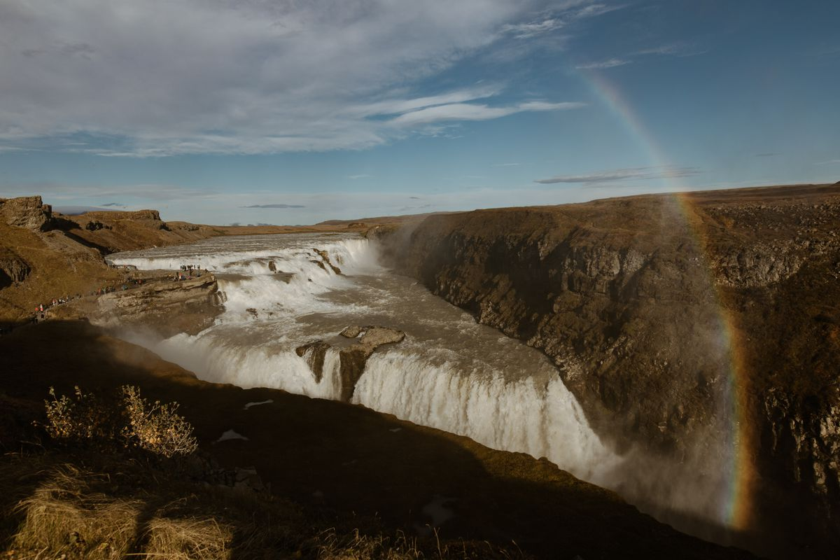 A waterfall in Iceland with a rainbow arc.