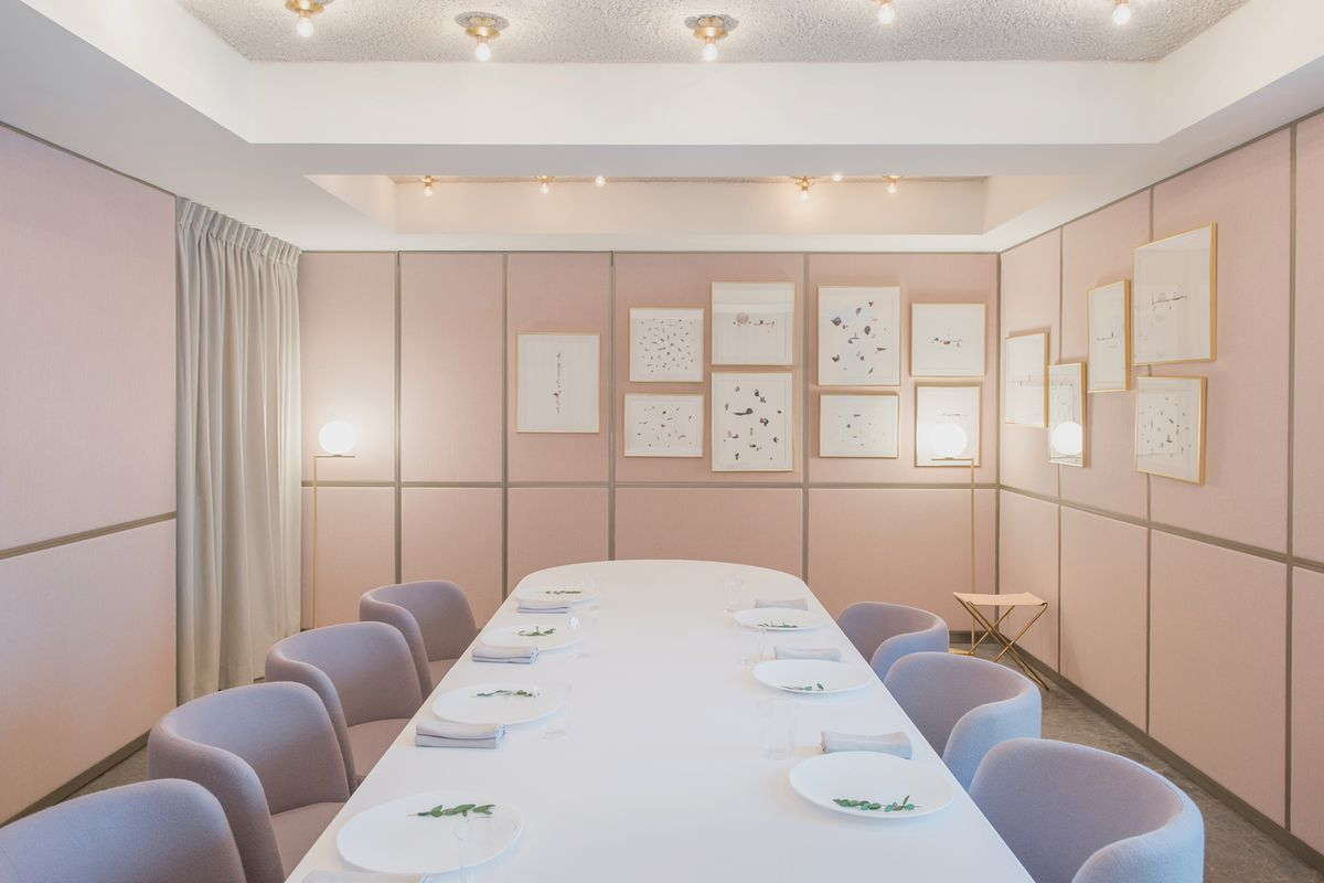 A long table in a private dining room set with plates