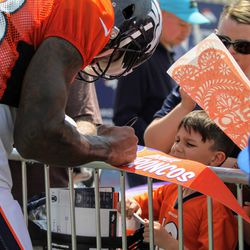 A young fan watched Demaryius Thomas sign an autograph.