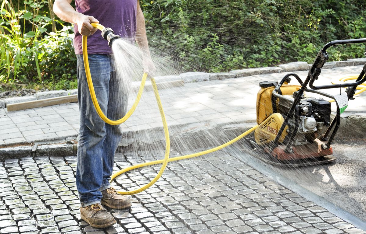Man Mists Cobblestone Driveway Apron With Water Hose Before Applying Grout