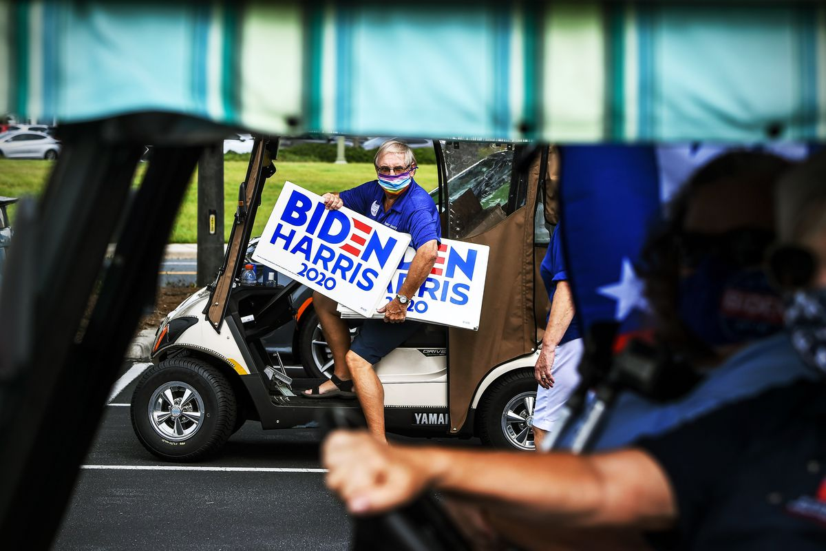 """A man in a golf cart with signs reading """"Biden/Harris 2020."""""""