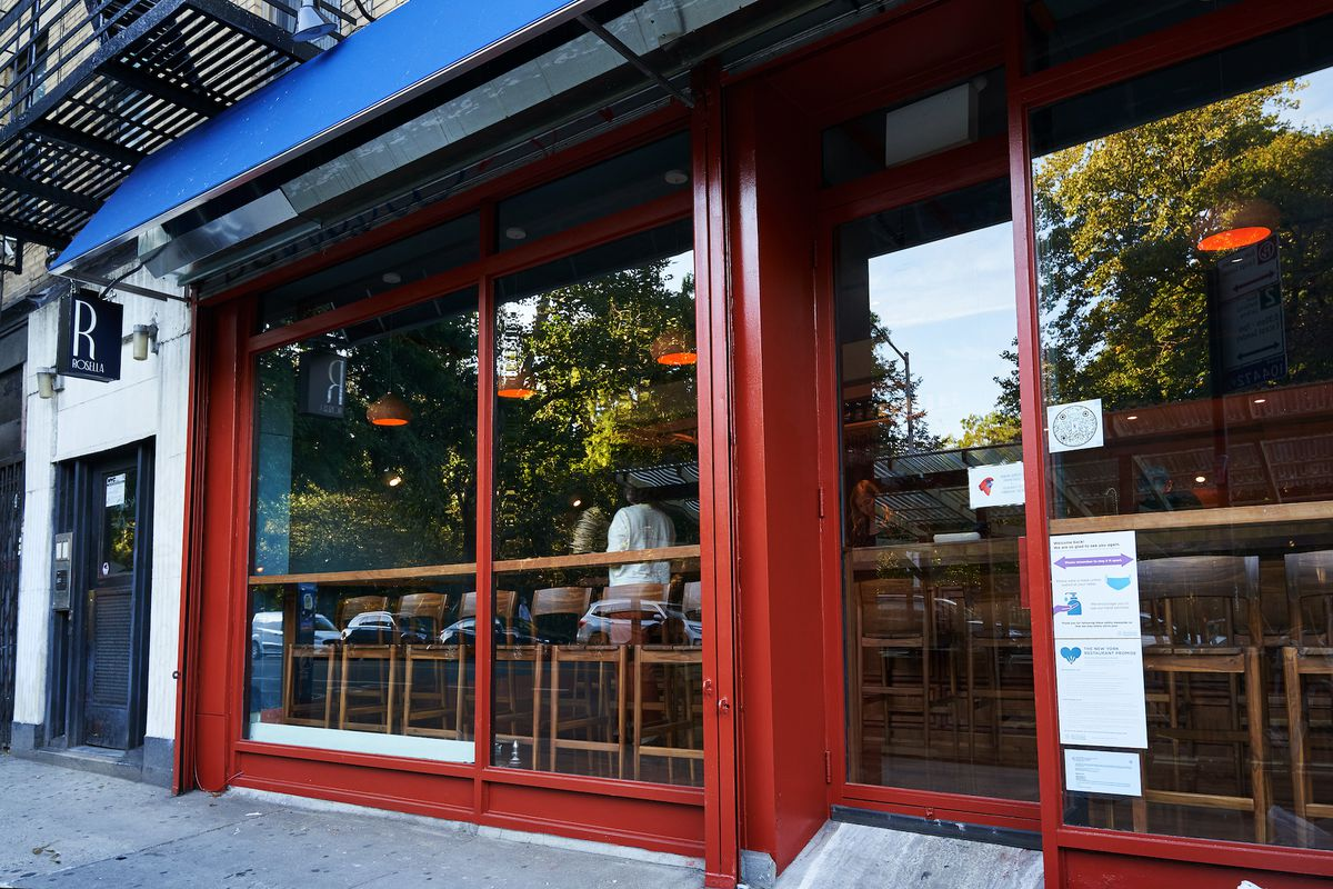 The exterior of a restaurant with large glass windows and red panels