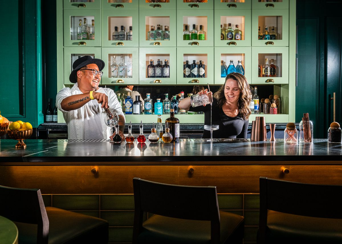The Wells bar director Philip Keath, left, and bartender Ashley Havens pour drinks