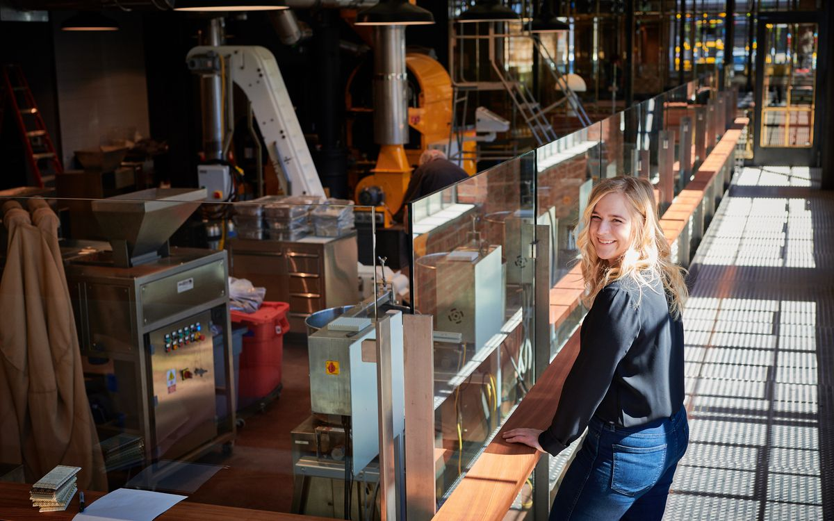 Annie looks over her shoulder while standing on a catwalk; the catwalk oversees chocolate-making equipment on the factory floor below.