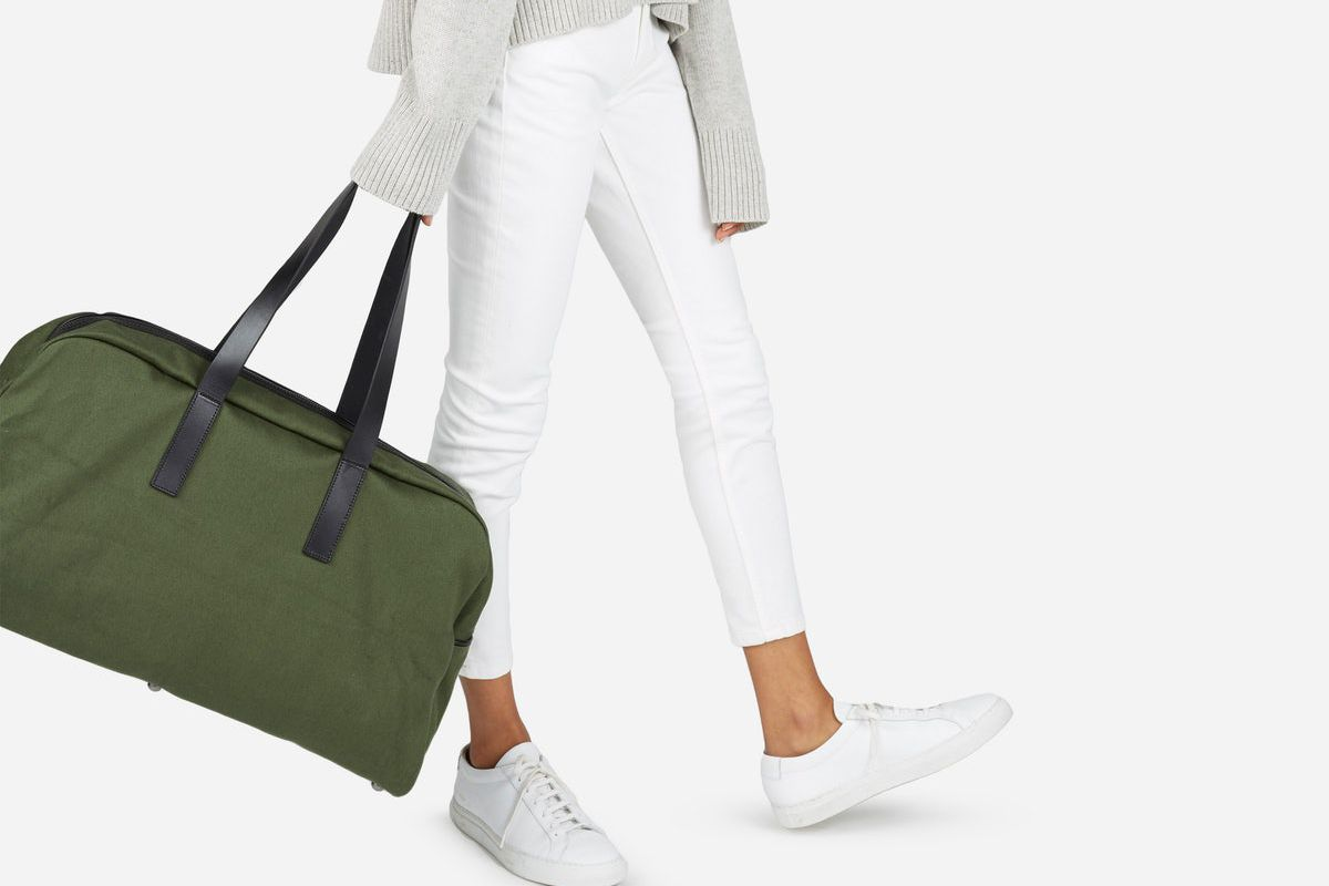 A model carrying Everlane's twill weekender bag.