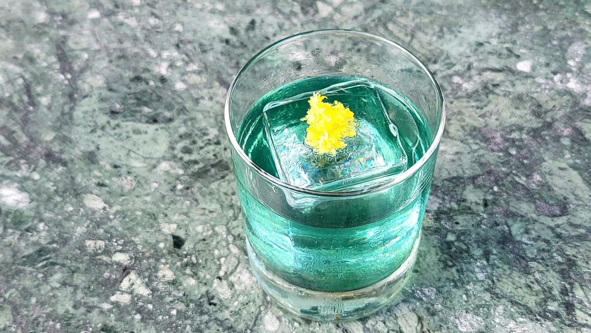 A tilted overhead shot of a light blue cocktail with a yellow garnish on a square ice cube.