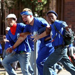 An injured opposition party Democratic Alliance (DA) supporter is helped by fellow members after being hit by a stone during their protest march against the Congress of South African Trade Unions (Cosatu) for opposing the youth wage subsidy in Johannesburg, South Africa on Tuesday May 15, 2012. An opposition party march in Johannesburg turned violent Tuesday after union supporters hurled rocks at the leader of South Africa's main opposition party.