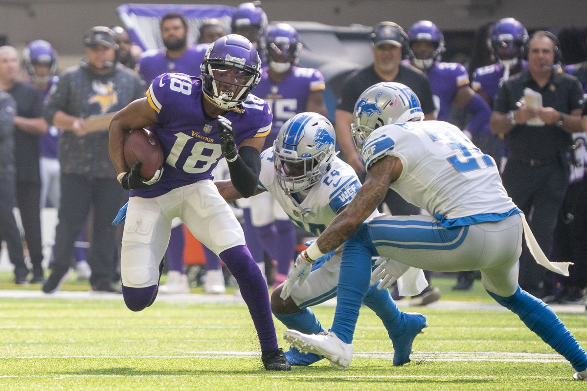 Minnesota Vikings wide receiver Justin Jefferson (18) advances the ball in the first quarter while pursued by Detroit Lions cornerback Amani Oruwariye (24) and safety Dean Marlowe (31) at U.S. Bank Stadium.