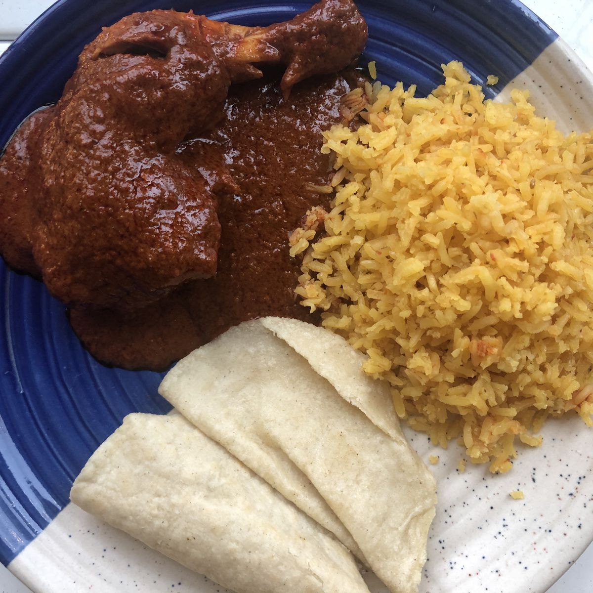 A plate of mole along with some white flour tortillas and yellow rice