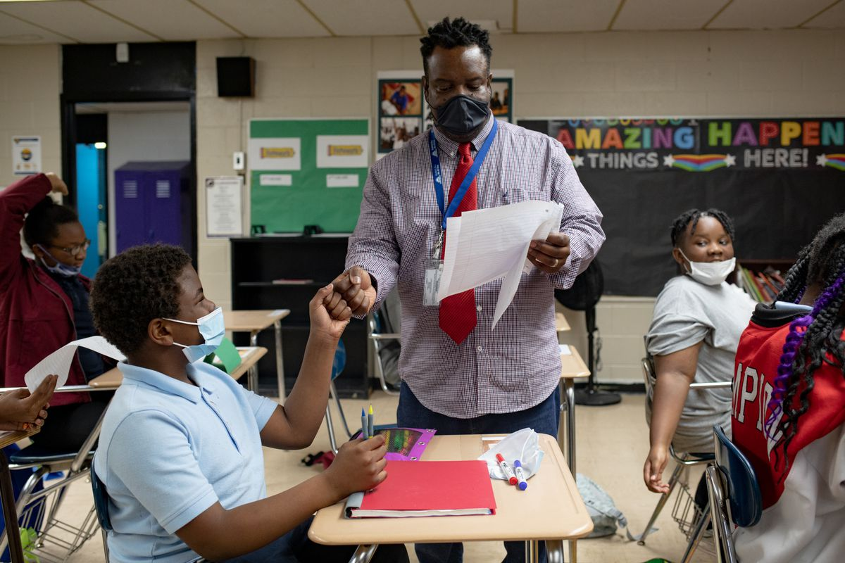 A teacher gives a fist bump to one of his students during a class exercise.