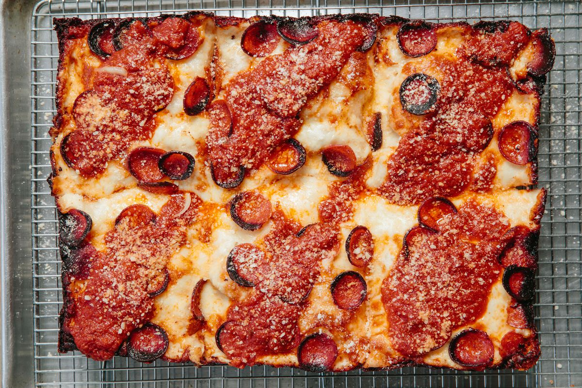Overhead view of a rectangular Detroit-style pizza topped with pepperonis with charred edges and swooshes of tomato sauce on each of six slices