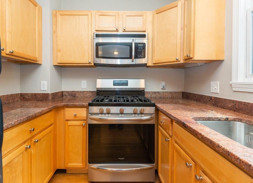 That kitchen, which has a U-shaped counter and a stove where the counters meet.