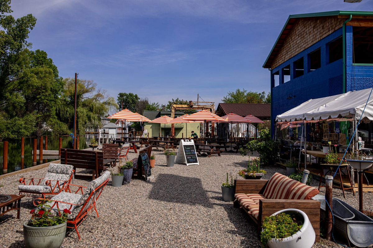 A blue building next to patio chairs, a fire pit, a couch, a tent with a coriander prep kitchen and picnic tables with parasols in the distance.
