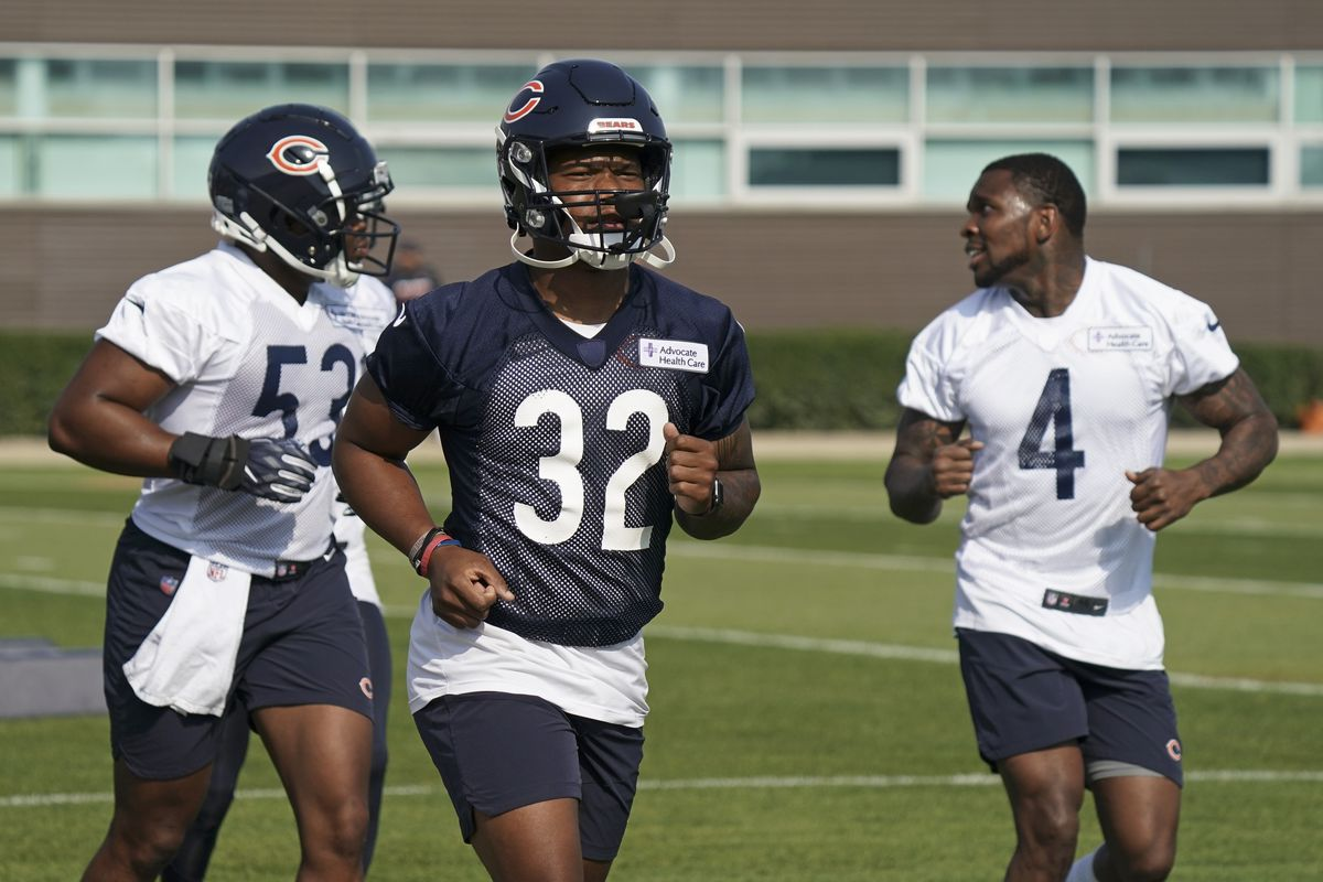 Ledarius Mack #53, David Montgomery #32, and Eddie Jackson #4 of the Chicago Bears run on the field during training camp at Halas Hall on July 29, 2021 in Lake Forest, Illinois.