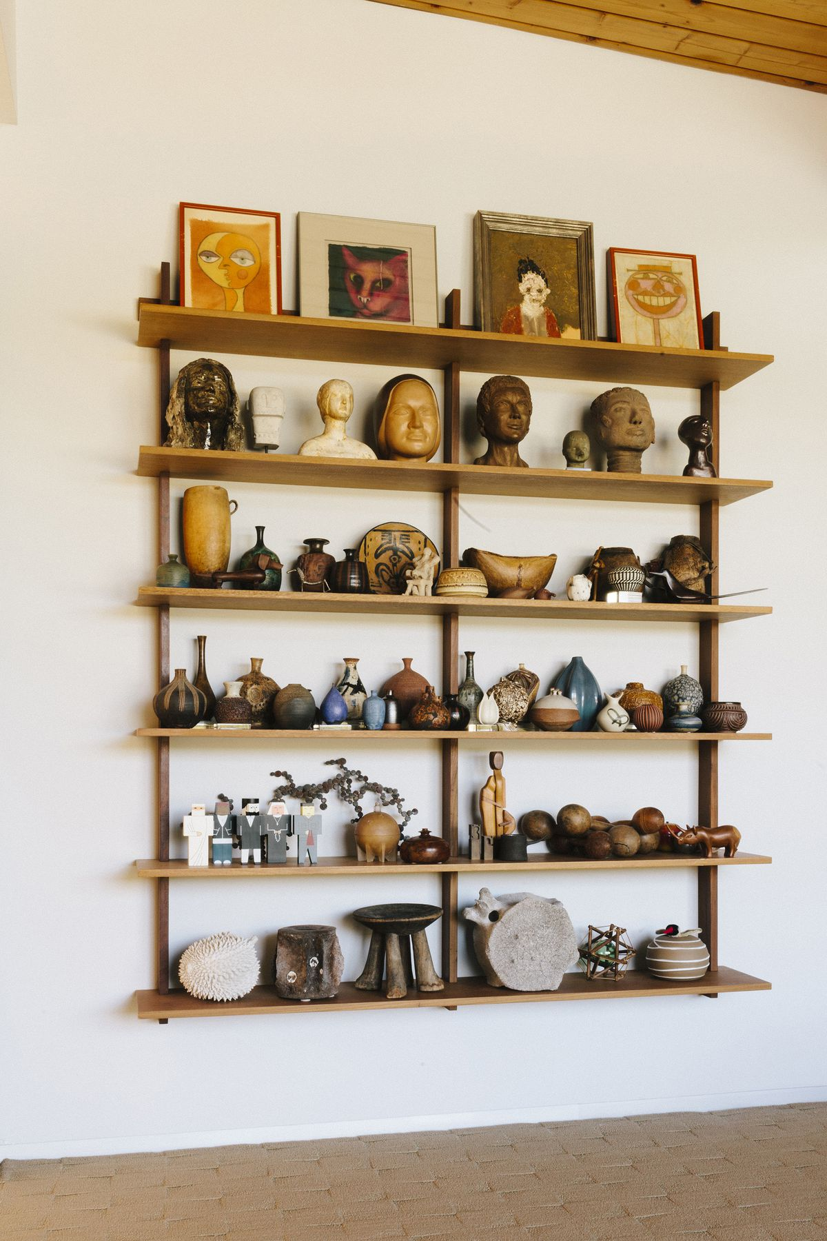 Wooden shelves with various art objects and framed prints against a white wall.