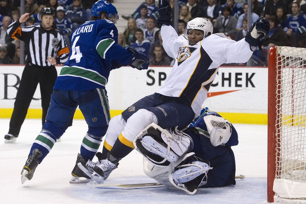 """Shortly after committing """"goaltender interference"""" and falling into the net, Joel Ward was speared in the face by Vancouver defenseman Keith Ballard (left)."""