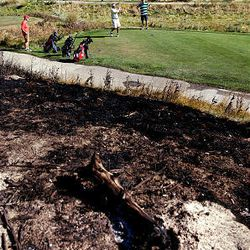 A golf game goes on Friday despite grass charred by a wildfire at Wingpointe Golf Course in Salt Lake City.