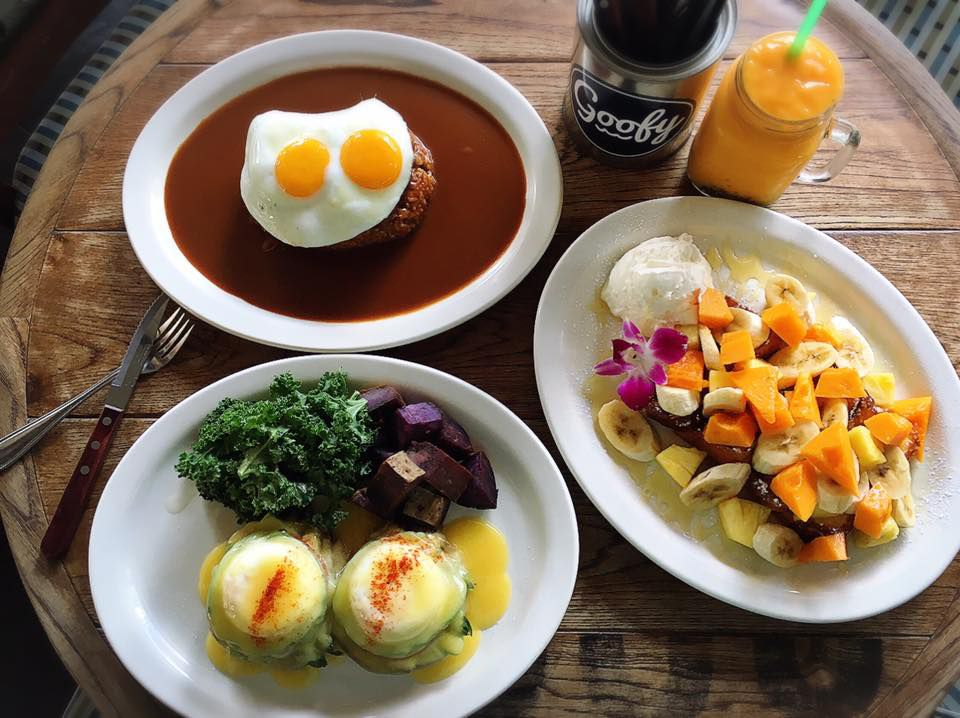 From above, a barrel-like table topped with a dish of eggs benedict with salad, french toast covered in fruit, and loco moco
