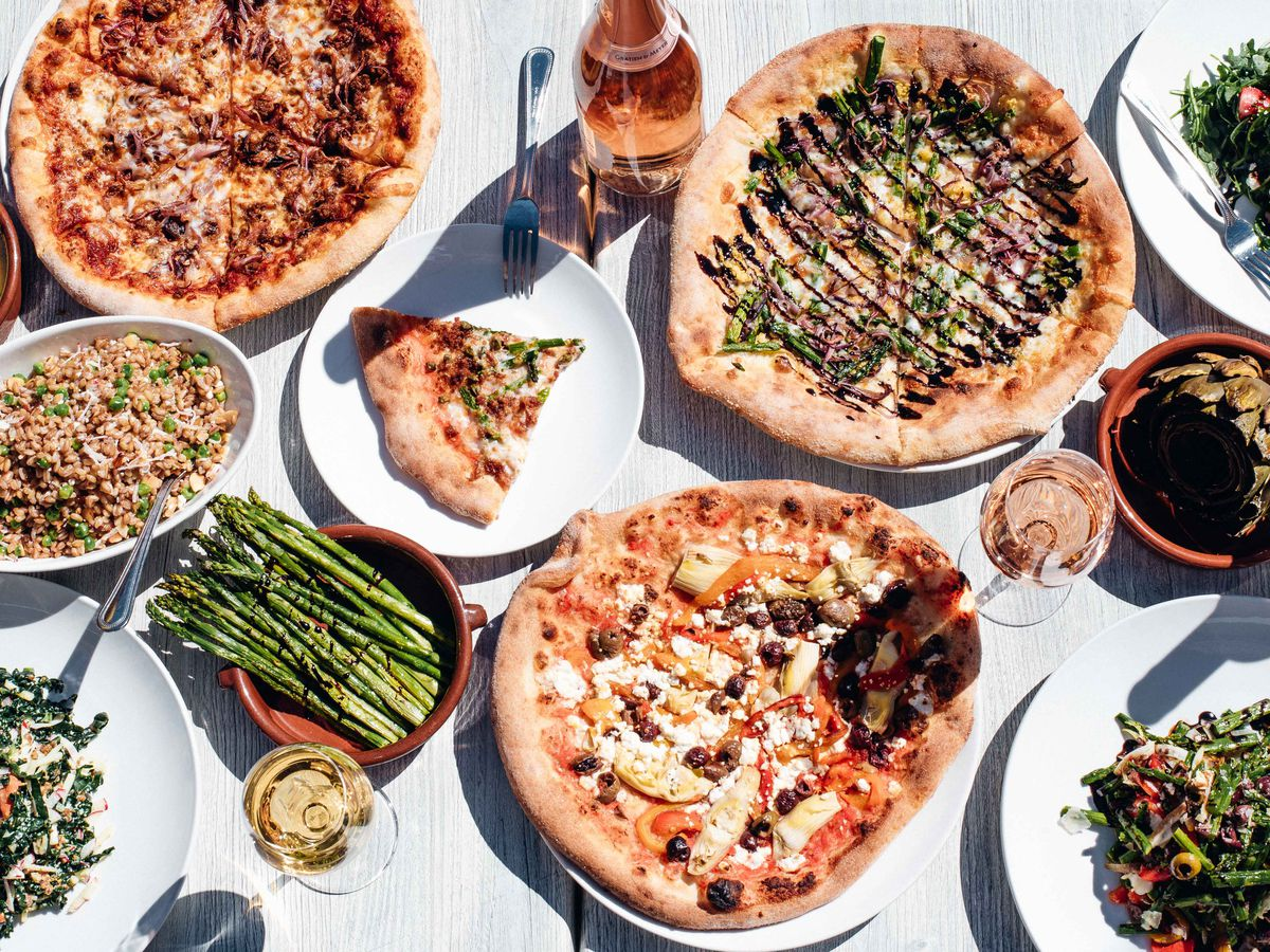 A table full of full pizzas, individual slices, asparagus, farro, salads, wine, and dressings
