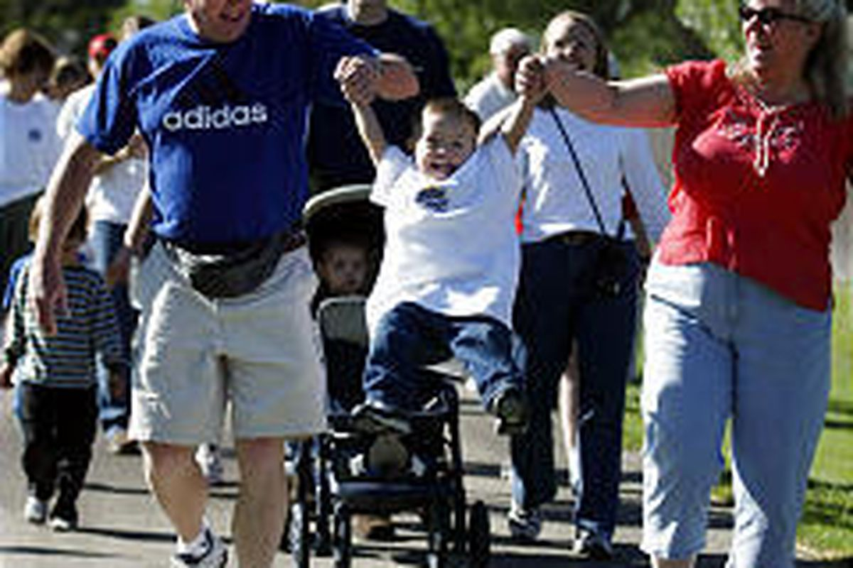 Jim and Melinda Reed lift grandson Jeffrey Miner during walk for people with Down syndrome.