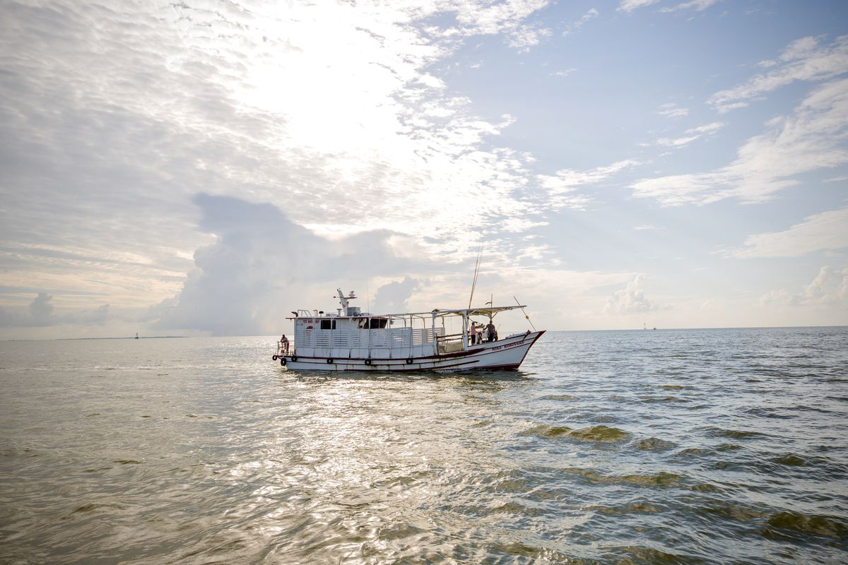 An oyster boat sits in the waters of the Gulf. The sun is shining, and there are clouds overhead