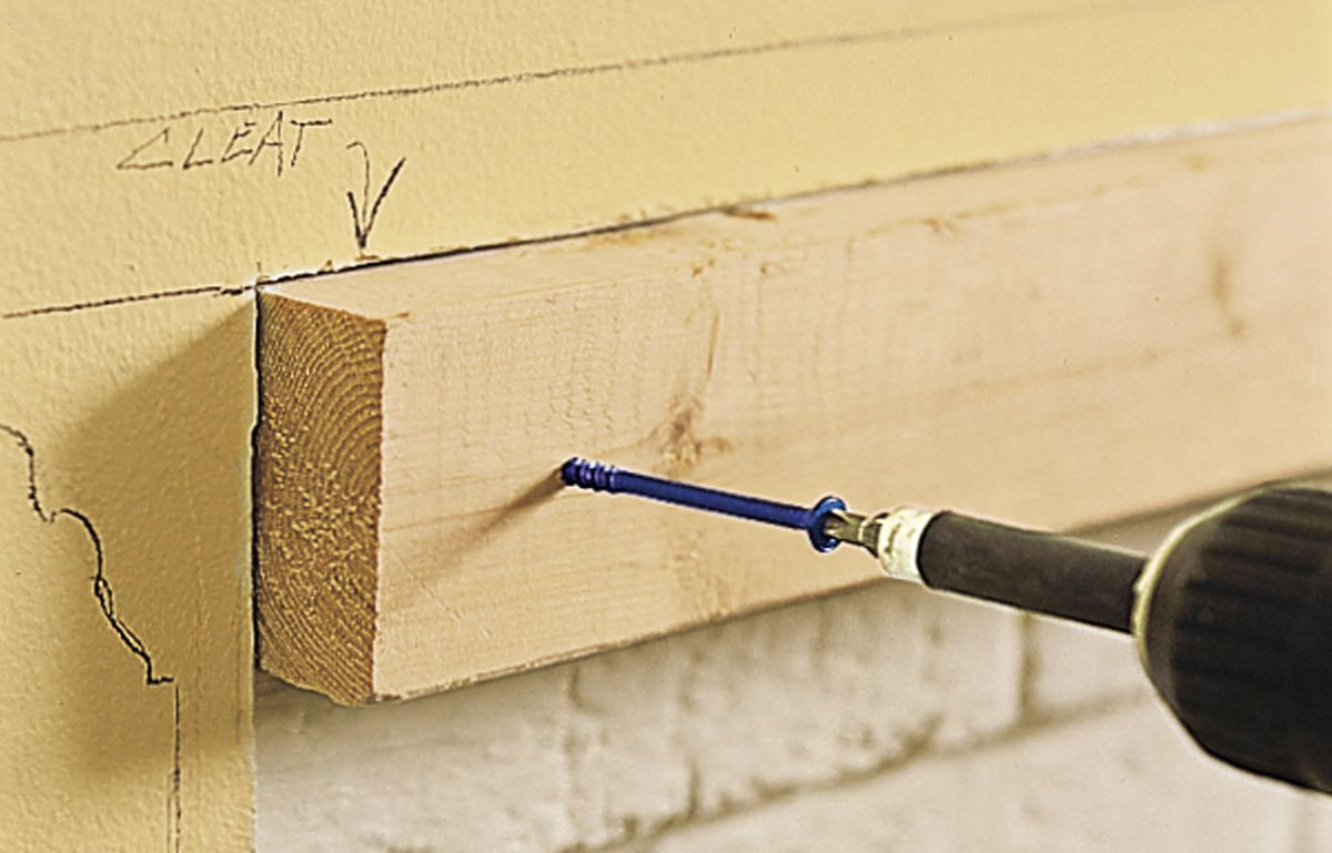Man Attaches Cleats To Brick With Concrete Screws In Preparation For Mantel