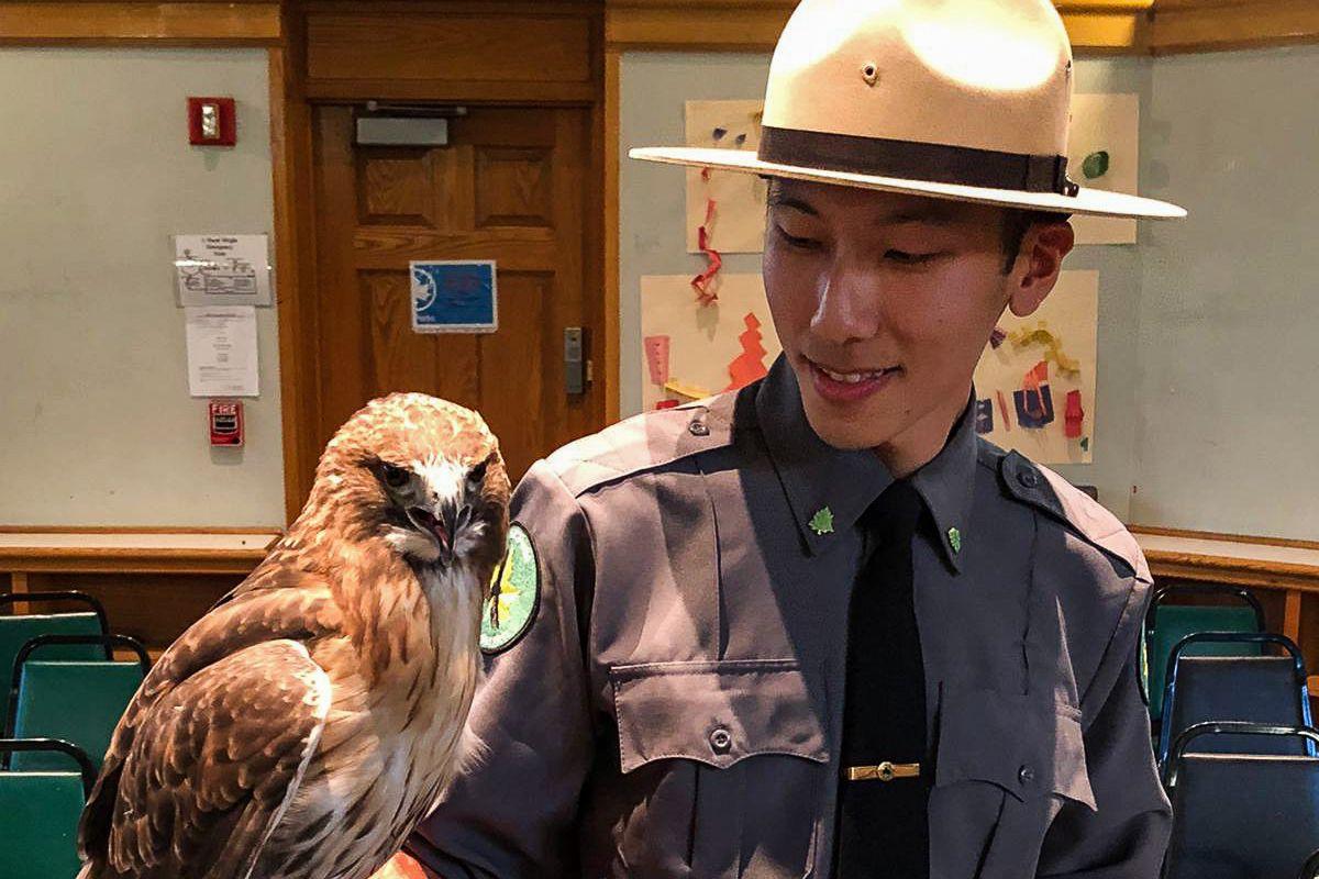 Urban Park Ranger Eric Zou teaches a lesson with a hawk.